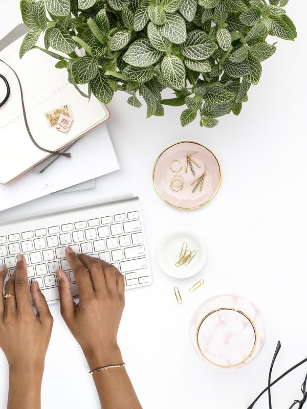 Stock Image of a blush pink styled office desktop with palms and greenery.